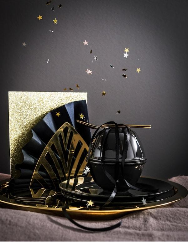 Vajilla dorada GLATTIS de IKEA y artículos de mesa VARDAGEN negros ordenados con papel brillante y ventiladores de servilletas de papel.