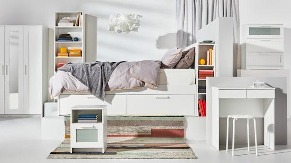 Valkoinen BRIMNES-sänky jonka yläpuolella roikkuu valkoinen kattovalaisin. Sängyn alla on kaksi isoa vetolaatikkoa.