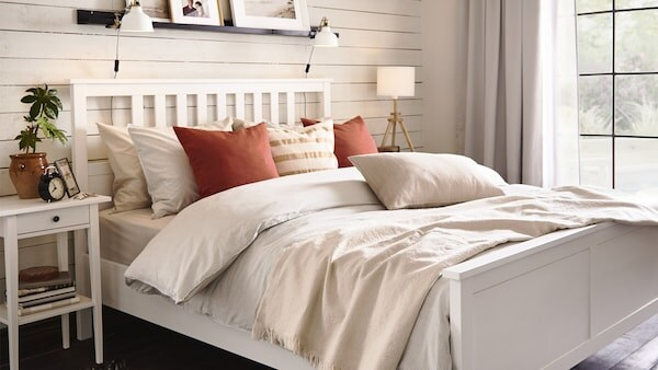 Valkoinen HEMNES-sänky jossa on vaaleat lakanat. Sängyn päällä on paljon koristetyynyjä.