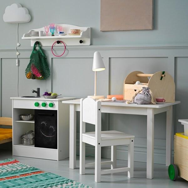 Valkoinen lastenpöytä ja lastentuoli. Pöydällä on pöytävalaisin ja askarteluvälineitä. Vieressä valkoinen leikkikeittiö.