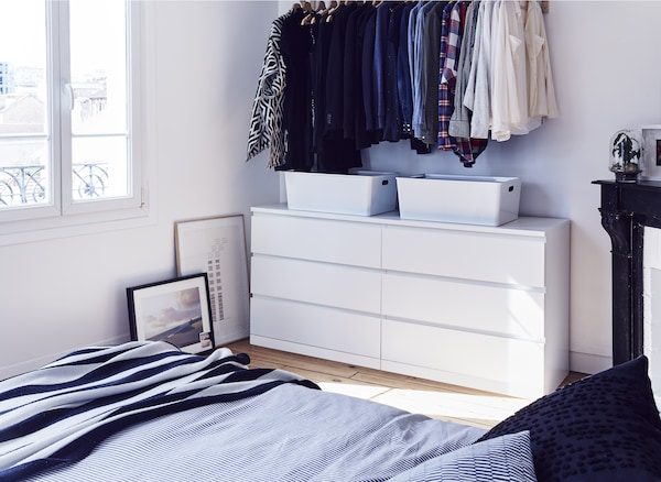 Valkoinen lipasto ja vaatteet makuuhuoneessa.