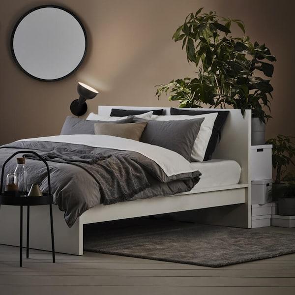 Valkoinen MALM-sänky tummassa makuuhuoneessa. Seinällä on pyöreä peili ja sängyn päädyssä on iso kasvi.