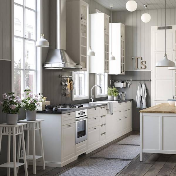 Valkoinen METOD/MAXIMERA -keittiö, jossa BODBYN-vitriiniovet ja seinään kiinnitettävä FÖLJANDE-liesituuletin.