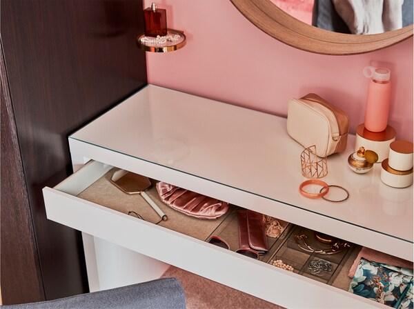 Valkoinen peilipöytä ja pyöreä peili. Peilipöydänlaatikosta pilkistää koruja.