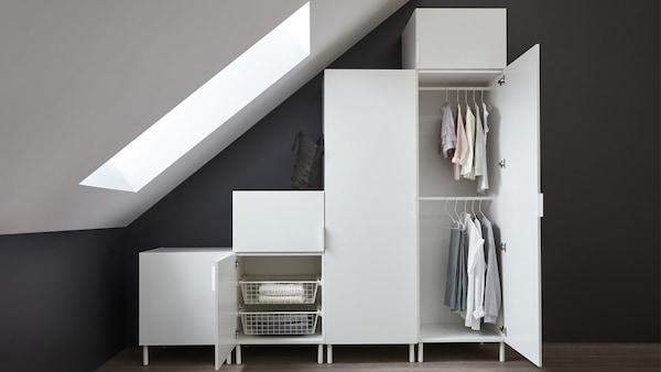 Valkoinen PLATSA-kokonaisuus. Kokonaisuudessa on pari ovea auki, joista näkee että kaapeissa on vaatteita viikattuna ja henkareissa roikkumassa.