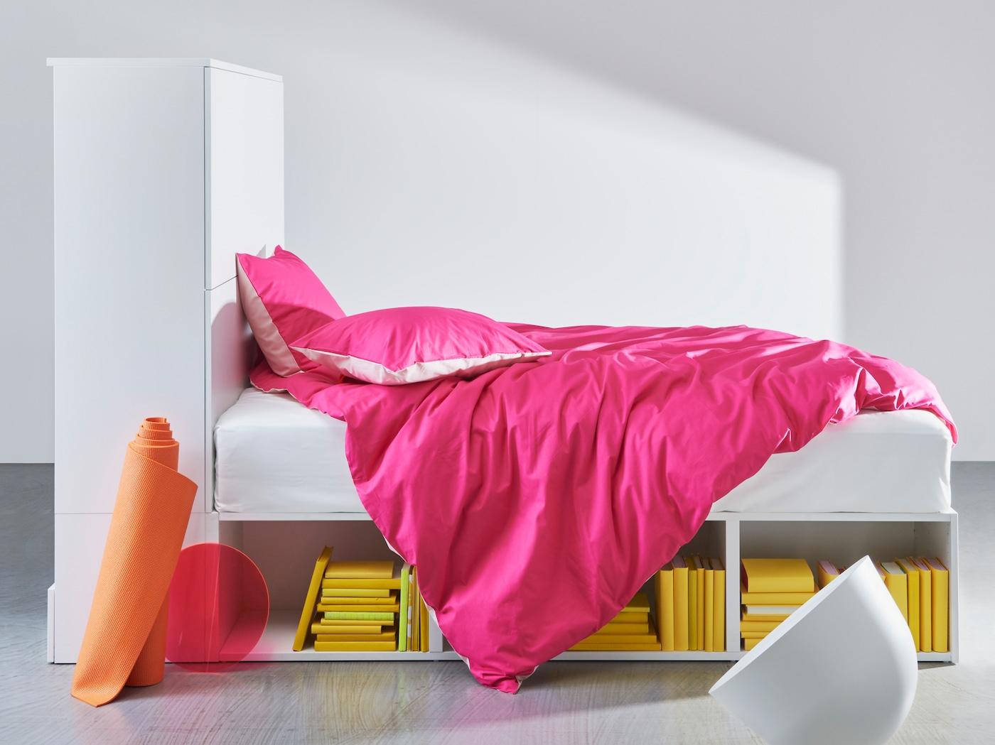 Valkoinen PLATSA- sängyn runko, jonka alla on avointa säilytsytilaa ja toisessa päässä on säilytystilaa ovien takana.