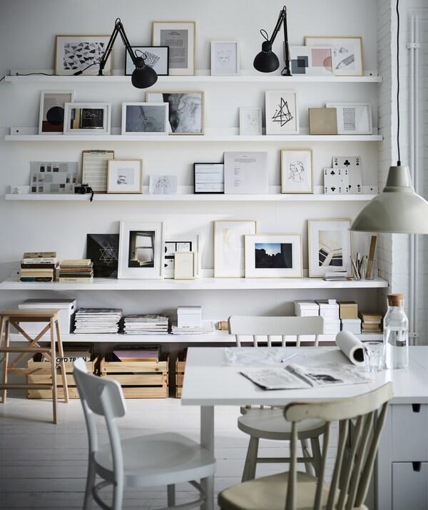 Valkoinen pöytä, jonka takana on tauluseinä aseteltuina valkoisille tauluhyllyille ja hyllyille.