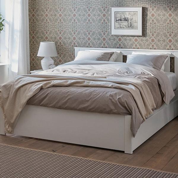 Valkoinen sänky, keskellä makuuhuonetta. Sängyssä on vaalet harmaan sävyiset lakanat.