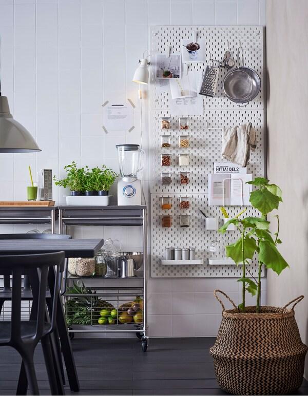 Valkoinen SKÅDIS-säilytystaulu on kiinnitetty keittiön seinään. Viereisellä työtasolla on blenderi, reseptejä ja smoothie-aineksia varten.