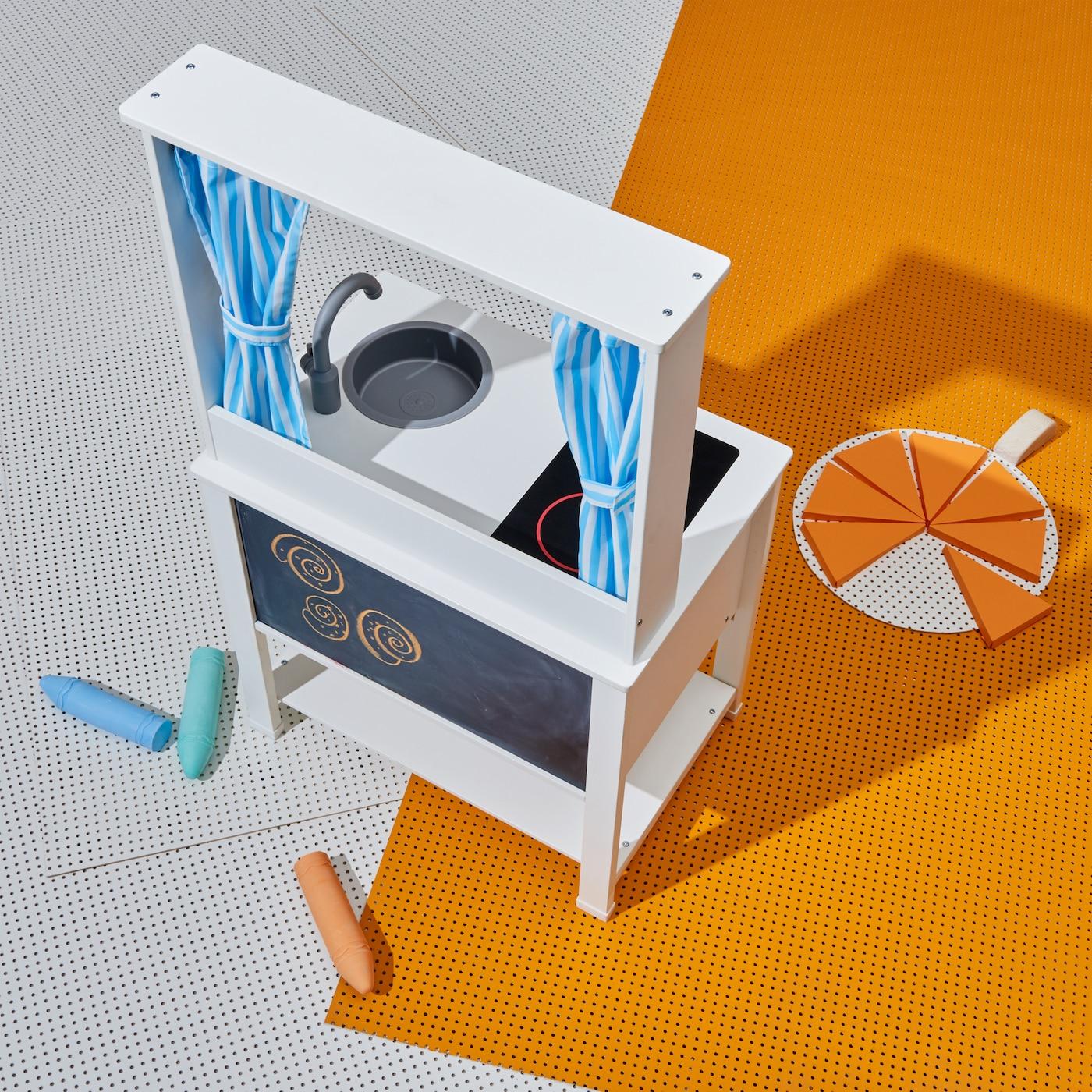 Valkoinen SPISIG leikkikeittiö, jonka toisella puolella on liitutaulu ja toisella puolella leikkikeittiö. Sinivalkoiset verhot erottavat osia.
