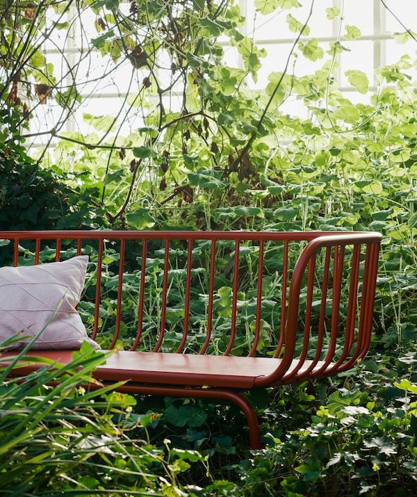 Valkoinen tyyny lepää viherkasvien ympäröimällä punaisella penkillä.