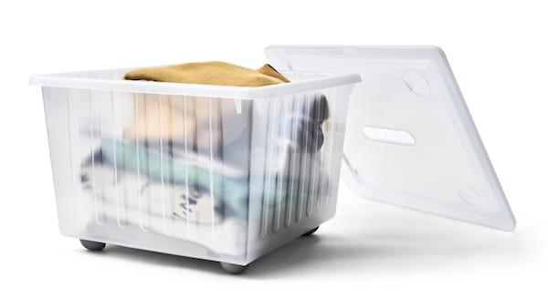 Valkoinen VESSLA-laatikko, jonka sisällä on viikattuna vaatteita.