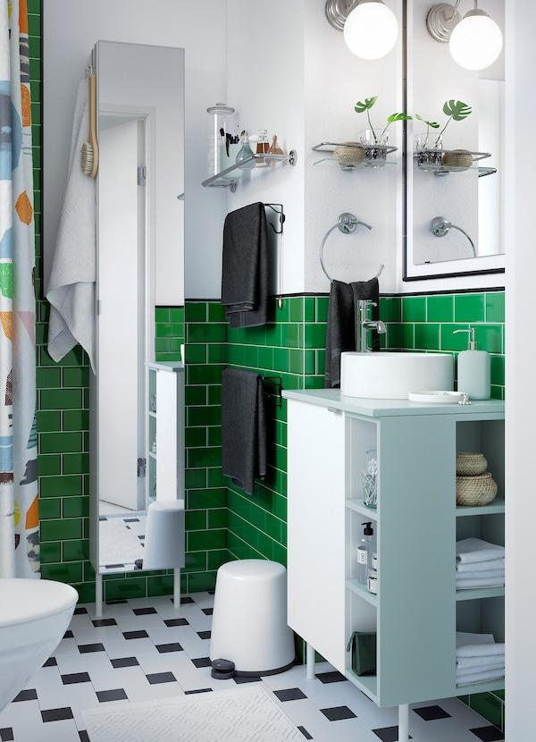 Valkoinen, vihreä ja musta kylpyhuone, jossa valkoinen allaskaappi ja avointa ja suljettua säilytystilaa.