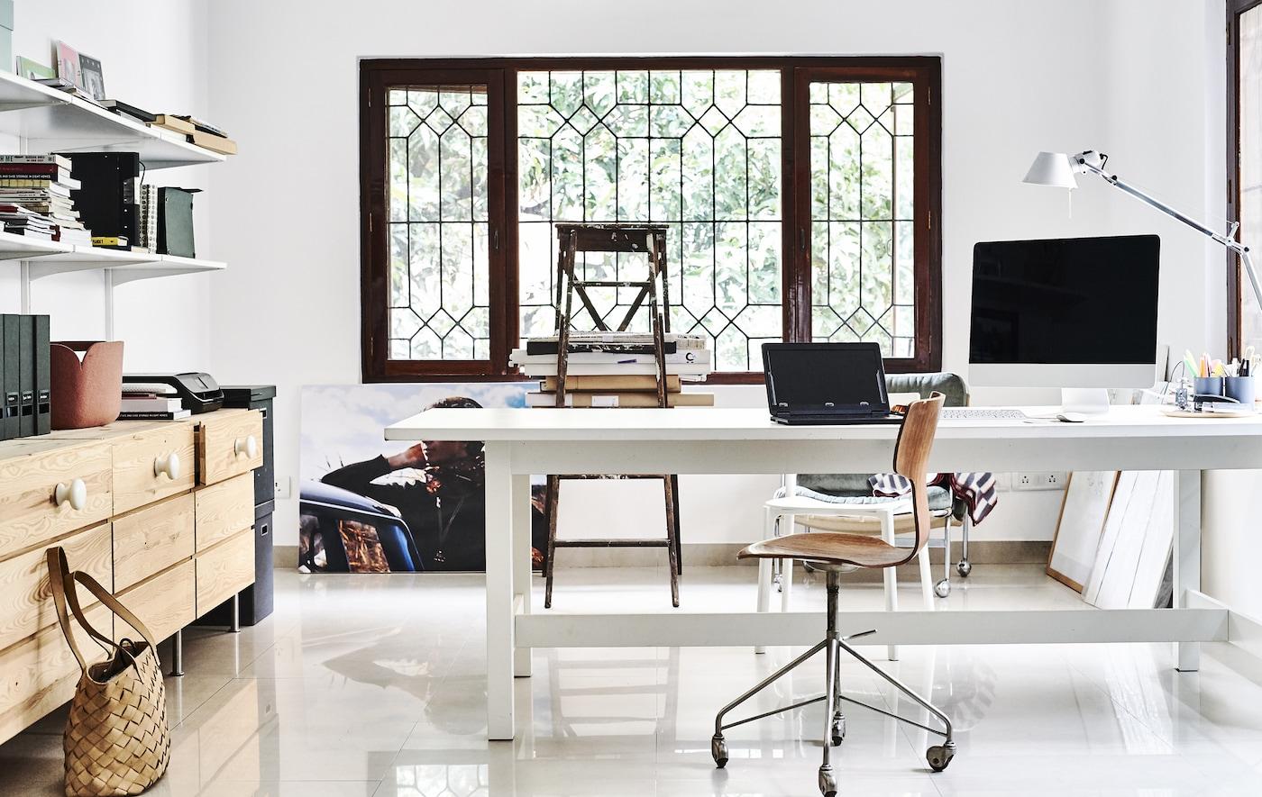 Valkoisen sävyillä sisustettu kotitoimisto, jossa puinen lipasto ja hyllyt.