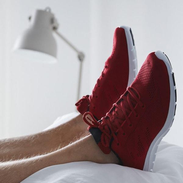 Valkoisen tyynypinon päällä lepää jalat punaisissa lenkkareissa.