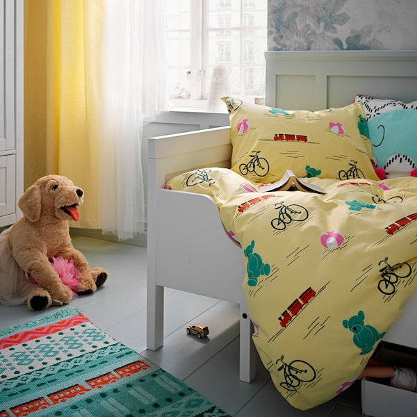Valkoisessa lastensängyssä peitto ja tyyny, jotka on pedattu lelukuvioisella, keltapohjaisella KÄPPHÄST-pussilakanasetillä. Sängyn vieressä lattialla värikäs matto ja koirapehmolelu.