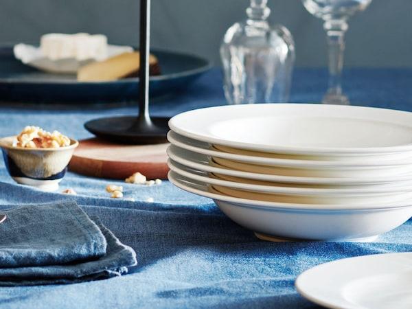 Valkoiset lautaset pöydällä sinisen pöytäliinan päällä