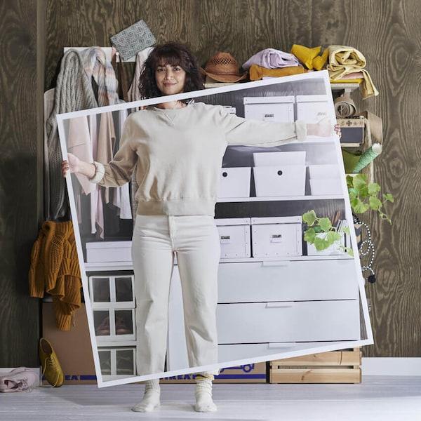 Valkoisissa vaatteissa oleva nainen seisoo sotkuisten hyllyjen edessä pitellen suurta kuvaa hyllyistä, kun ne on siivottu.