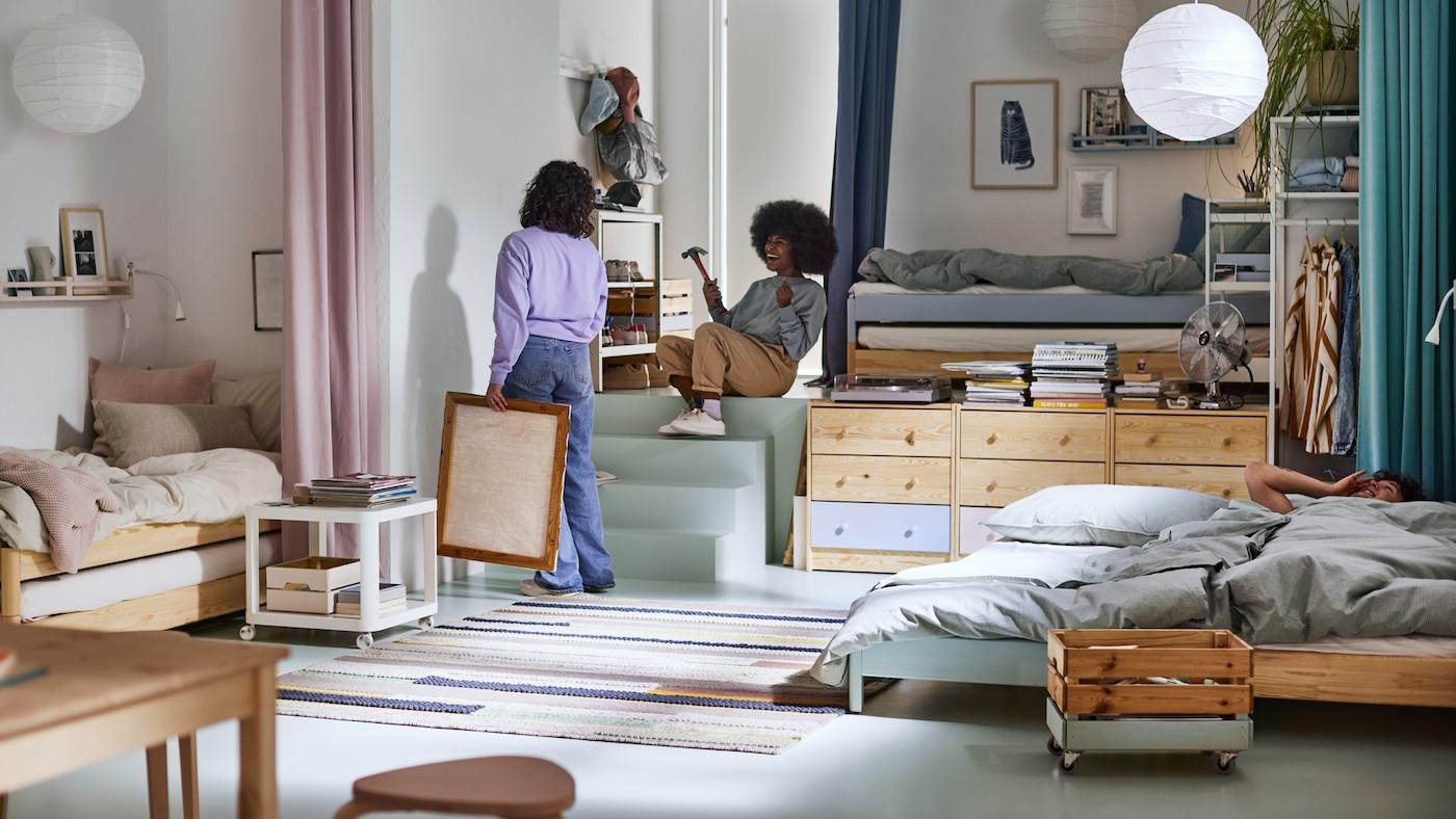 Valoisa huone, jossa on kaksi naista ripustamassa kuvaa seinälle ja mies makaamassa yhdessä kolmesta sängystä. Katosta roikkuu kaksi valkoista valaisinta ja lattialla on värikäs matto.