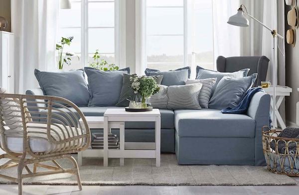 Valoisa olohuone, jossa on kulmasohva ja siihen täydellisesti mitoitettu matto.