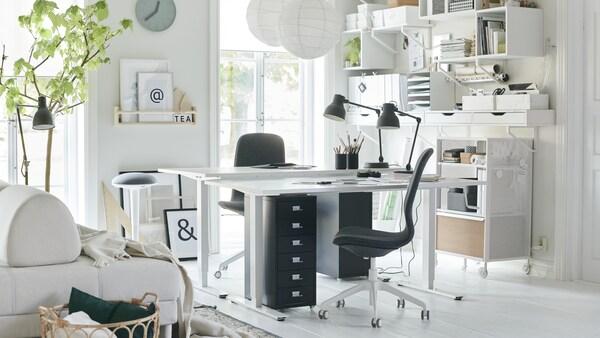 Valoisa pieni kahdenhengen toimistotila, jossa valkoiset sähkösäädettävät pöydät ja tummanharmaat tuolit.