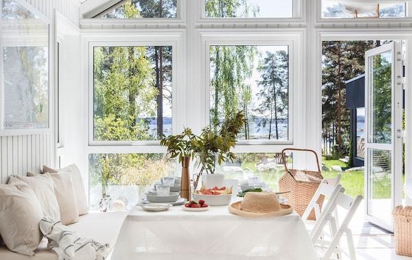Valoisa ruokailutila kesämökillä veden äärellä. Kuvassa näkyy penkki, pöytä, tuoleja sekä koreja ja kaunis merimaisema odottamassa ruokailijoita.