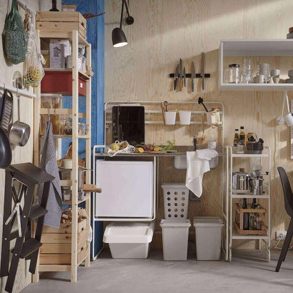 Vaneriseinäisessä keittiössä SUNNERSTA-minikeittiö, IVAR-hylly, pöytä ja tuolit.