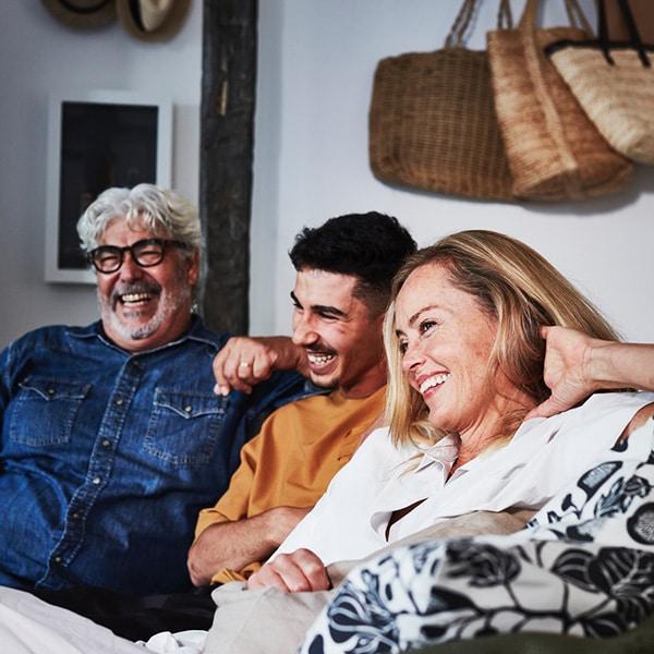 Vanhempi mies, nuorimies ja nainen istuvat sohvalla ja nauravat yhdessä.