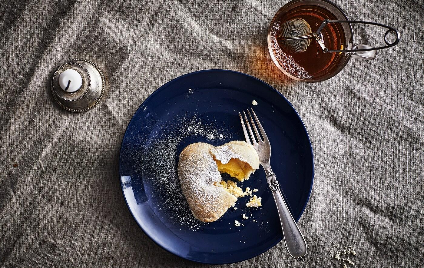 Ванильное печенье в виде сердечка, вилка на темно-синей тарелке, кружка с чаем и свеча.