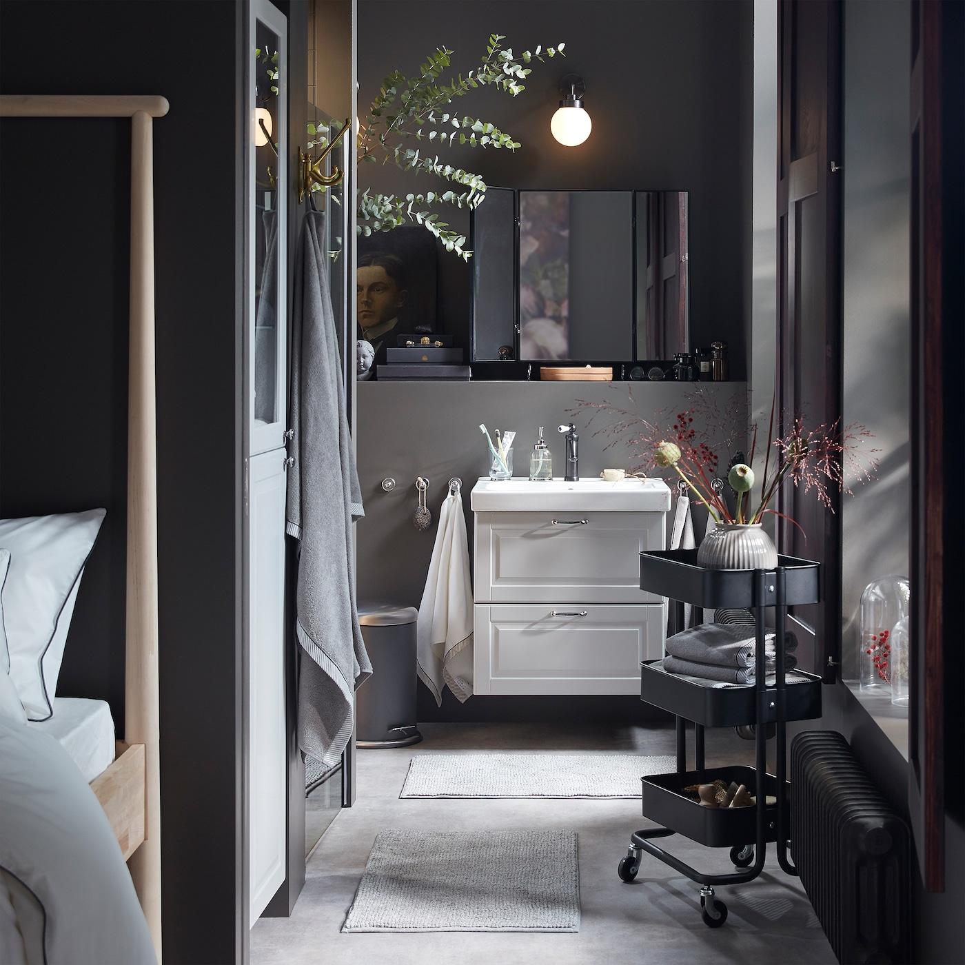 Ванная в серой цветовой гамме: шкаф под раковину и высокий шкаф светло-серого цвета, черная тележка и обилие декоративных сухих цветов.