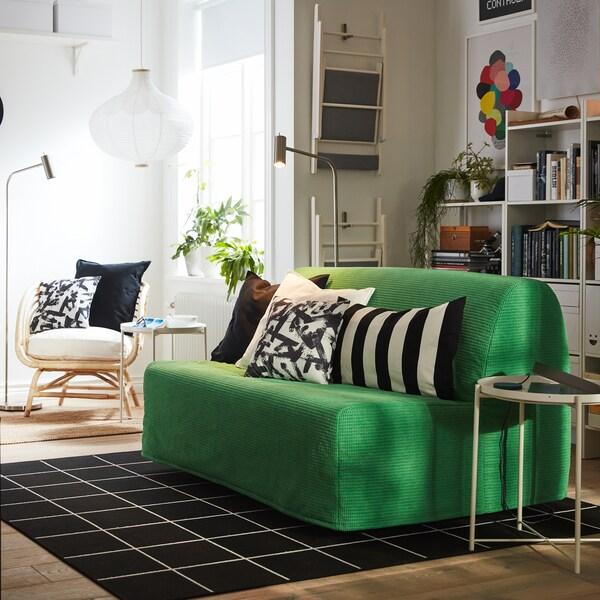 Vansbro 반스브로 브라이트그린 2인용 소파베드, 블랙과 화이트 텍스타일, 화이트 책장, 암체어가 있는 작은 원룸.