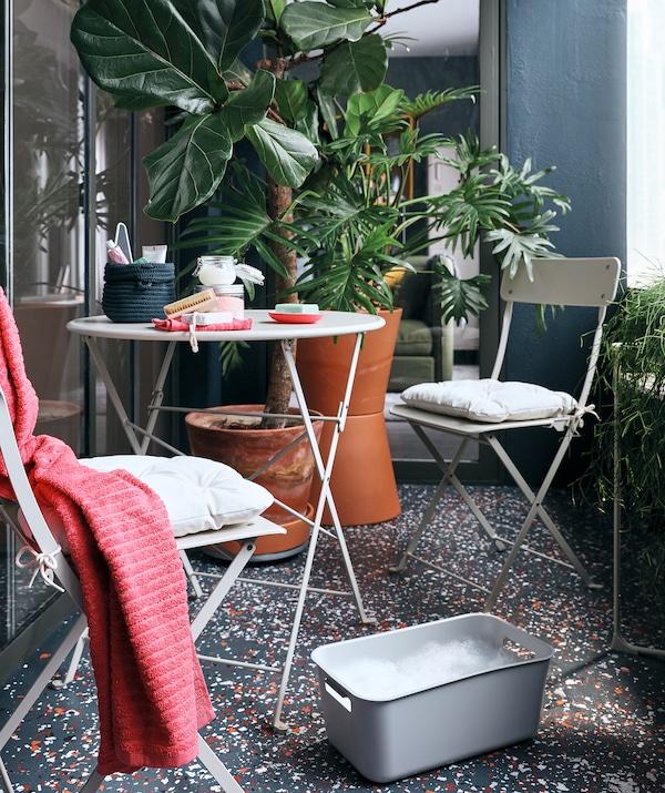 Varanda com plantas grandes em vasos, uma mesa redonda pequena e duas cadeiras e uma caixa GRUNDVATTNET para mergulhar os pés, junto a uma cadeira SALTHOLMEN.