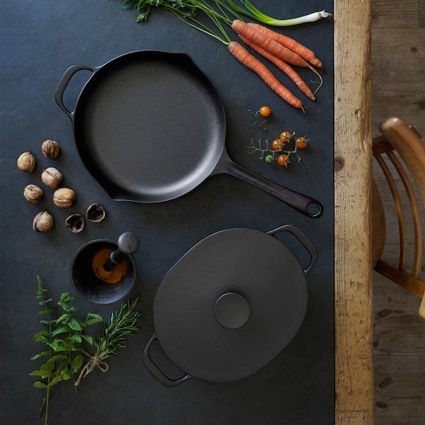 VARDAGEN posuda i tava na crnom drvenom stolu okružene su sastojcima za kuhanje kao što su mrkve i orašasti plodovi.