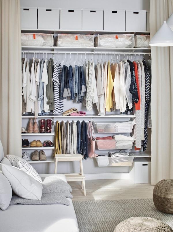 Vardagsrum där en vägg har öppna golvlånga gardiner som döljer en garderob som sträcker sig längs hela väggen.