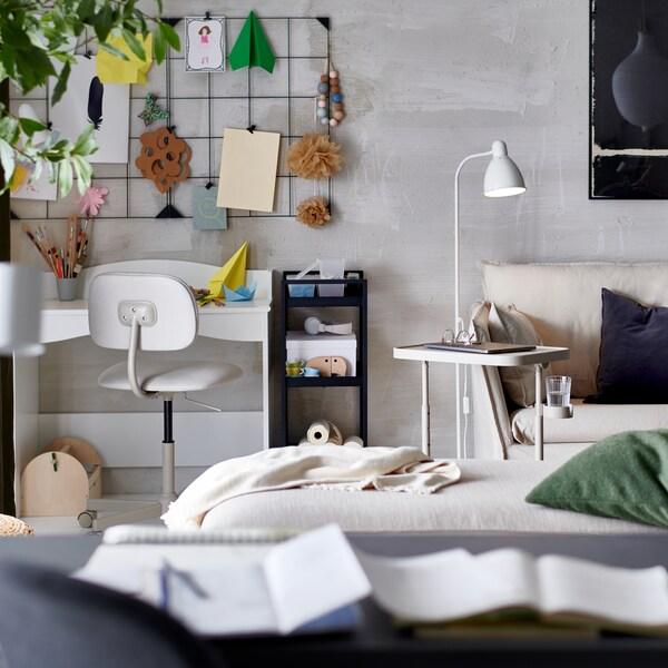 Vardagsrum i neutrala nyanser med ett vitt skrivbord och en arbetsstol i hörnet. På väggen ovanför syns en anslagstavla.