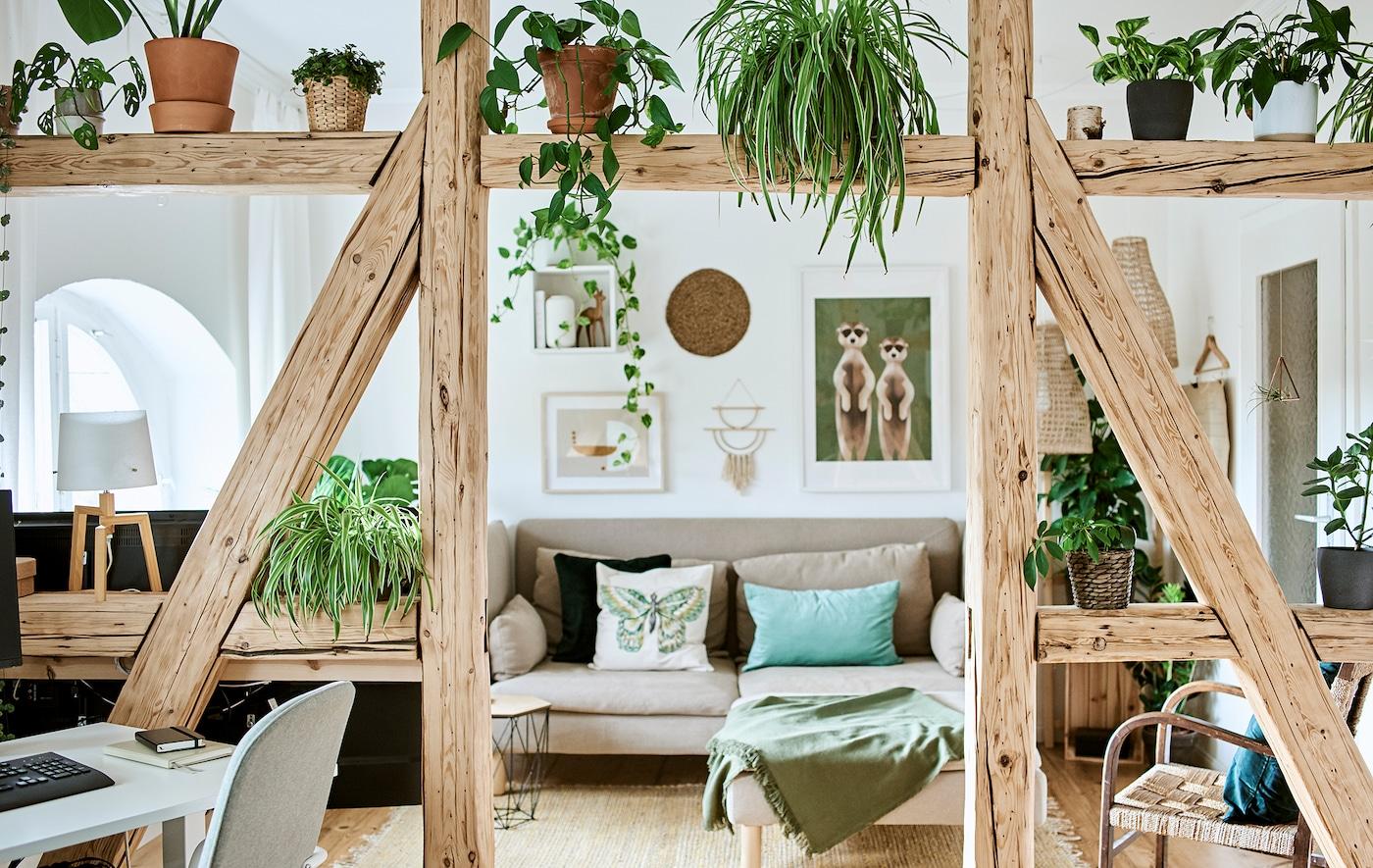 Vardagsrum med beige soffa och gröna kuddar vid en vägg med tavlor, A-formade bjälkar och växter fungerar som rumsavdelare för en arbetshörna.