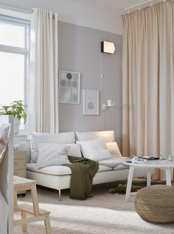 Vardagsrum med en ljus SÖDERHAMN soffa, ett soffbord och en puff. Den bortre väggen har fördragna gardiner från golv till tak.