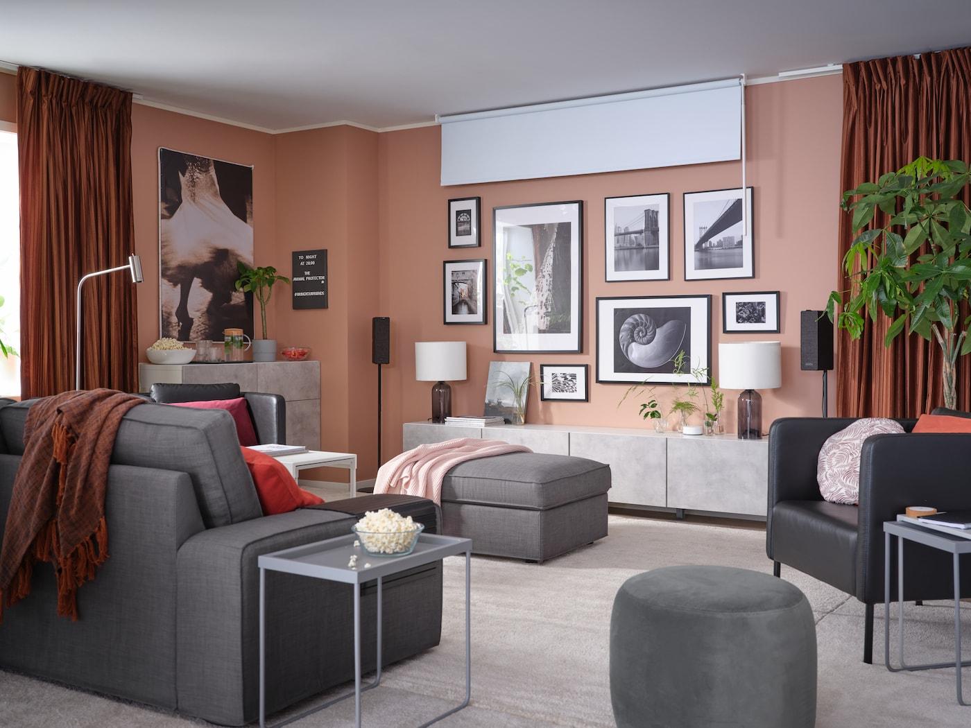 Vardagsrum med en vägg med inramad konst, mörkläggande rullgardin, rumsförmörkande gardiner och 3-sitssoffa.