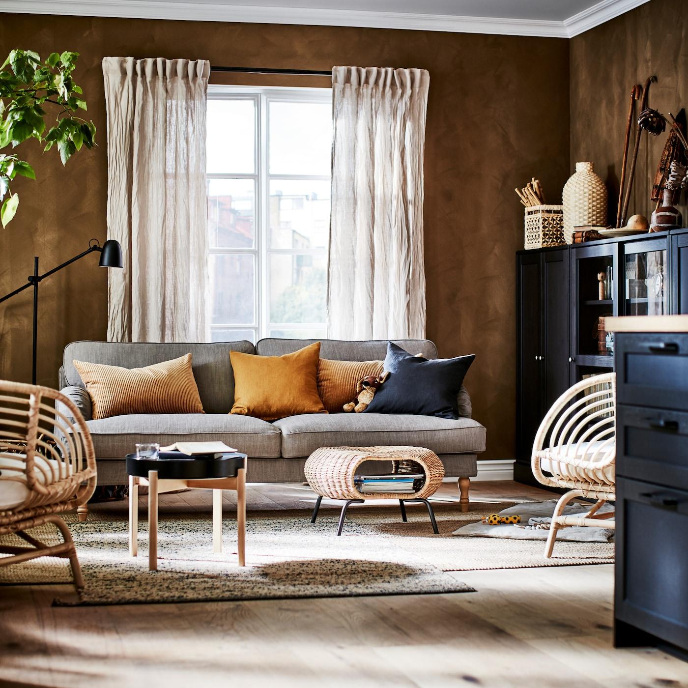 Vardagsrum med gråbeige soffa, två jutemattor, två rottingfåtöljer, beige linnegardiner och mörkbruna skåp.