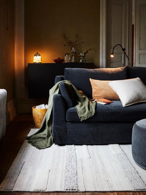 Vardagsrum med mörk soffa, cremevit matta, kuddar och filt, golvlampa och sideboard med dekorativa föremål.