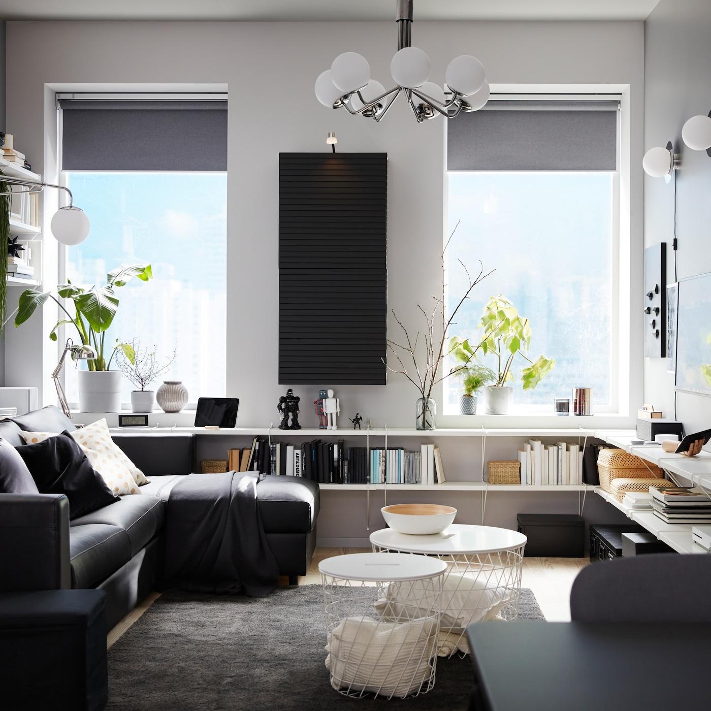 Vardagsrum med svart bäddsoffa med schäslong, vita hyllor, väggmonterat skåp i antracit samt mörkgrå matta.