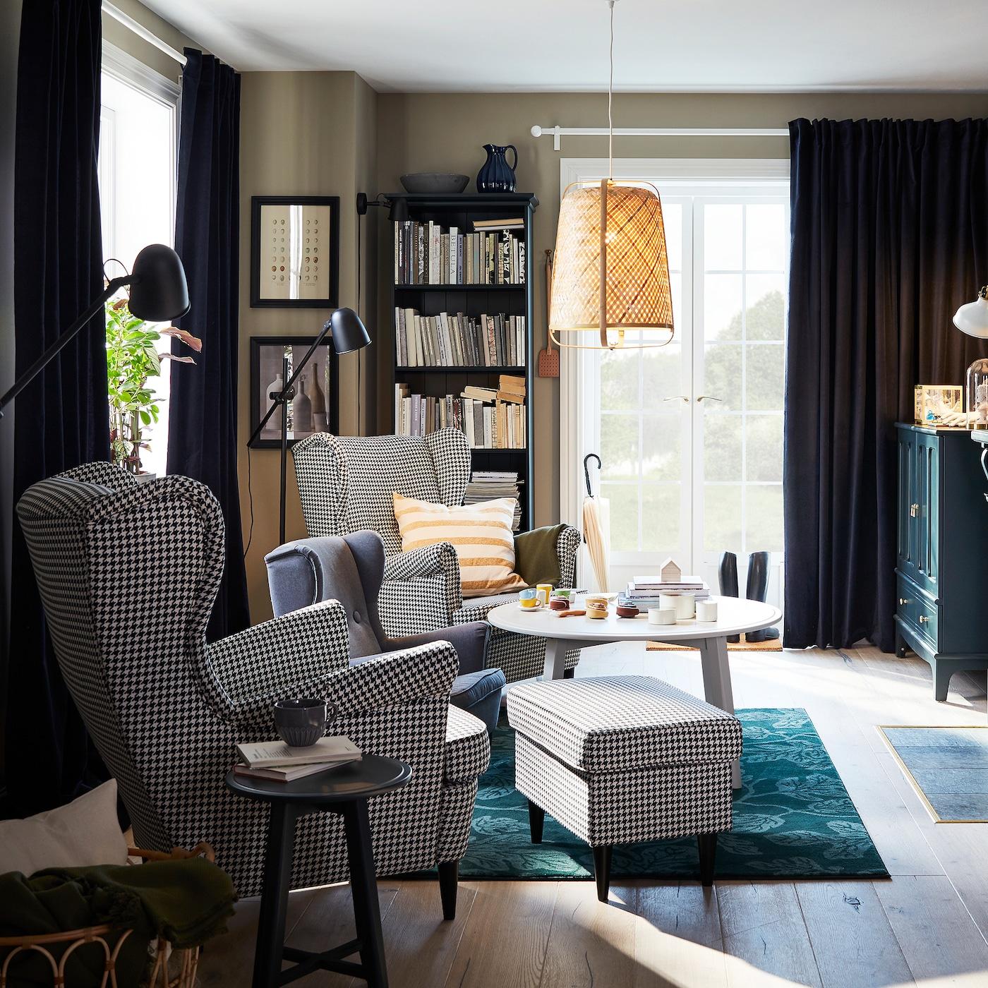 Vardagsrum med två hundtandsmönstrade öronlappsfåtöljer, grön matta, taklampa i bambu och runt soffbord.
