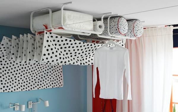 Varias barras para ropa MULIG en blanco montadas en el techo para guardar cosas y tender la colada.