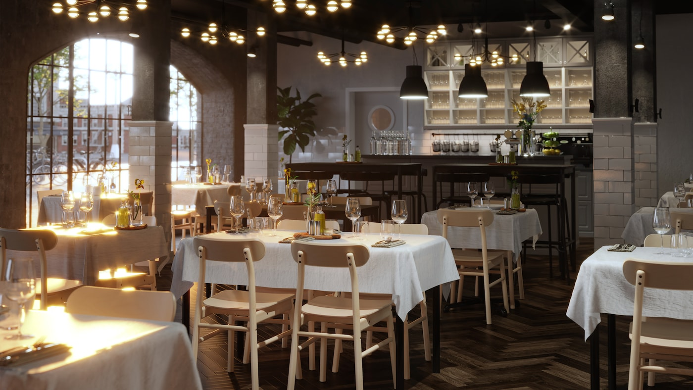 Varias mesas TOMMARYD bien dispuestas con manteles blancos, copas transparentes y flores en un restaurante espacioso.