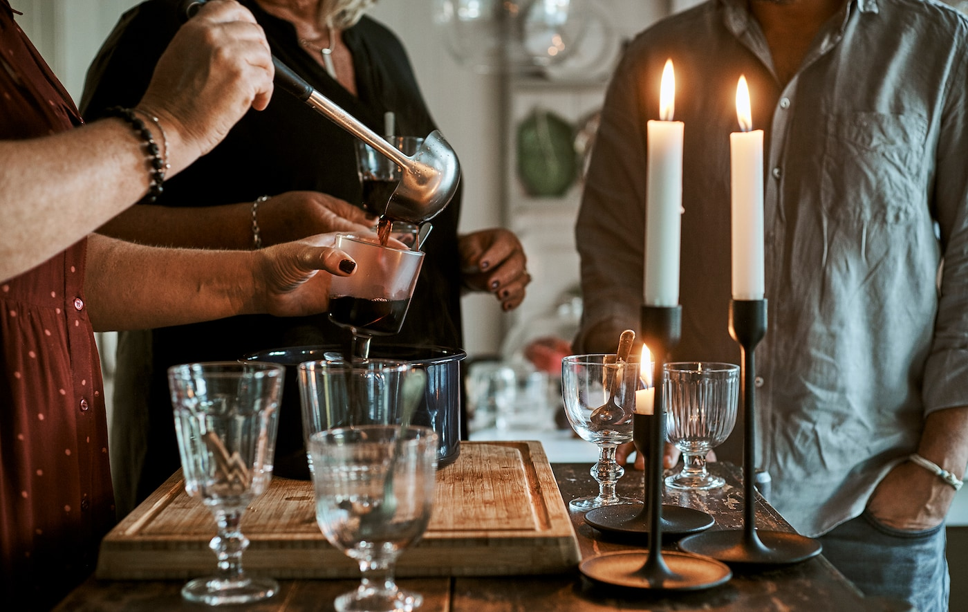 Varias personas de pie junto a una isla de cocina con vasos, velas encendidas y un recipiente con ponche caliente; una de ellas está echando la bebida en un vaso con un cazo.