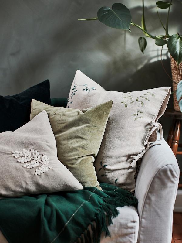 Varios cojines verdes y beige decorados con originales bordados de hojas. Se encuentran sobre un sofá gris claro.