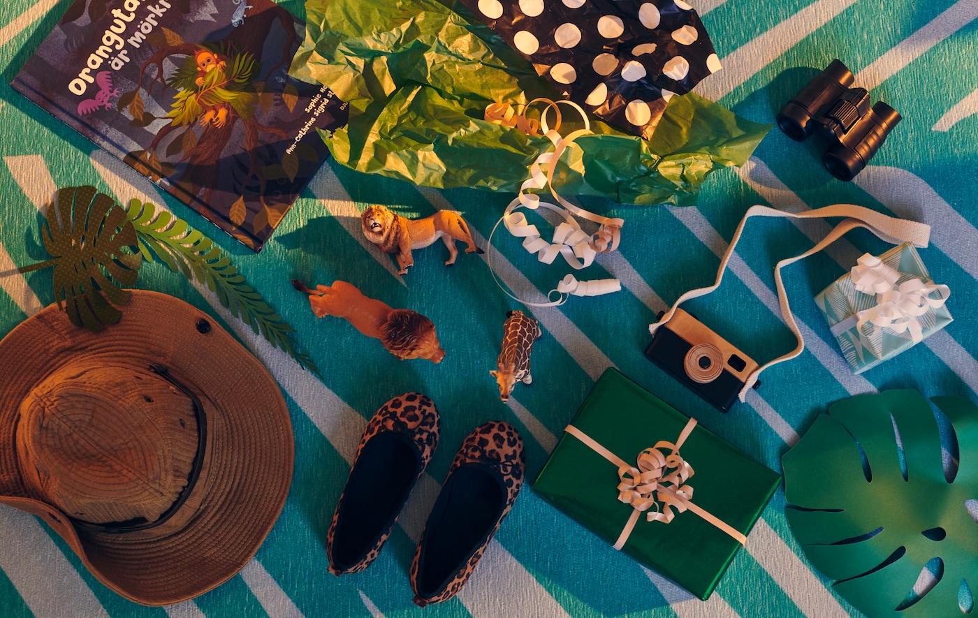 Vários presentes embrulhados e desembrulhados, e brinquedos adequados ao tema da exploração e aventura, em cima de um tapete GRACIÖS.