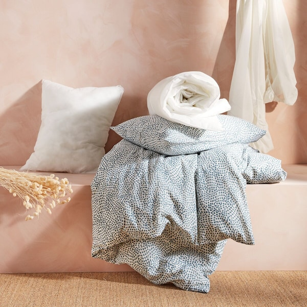 Various bedding textiles against a pale, terracotta background.