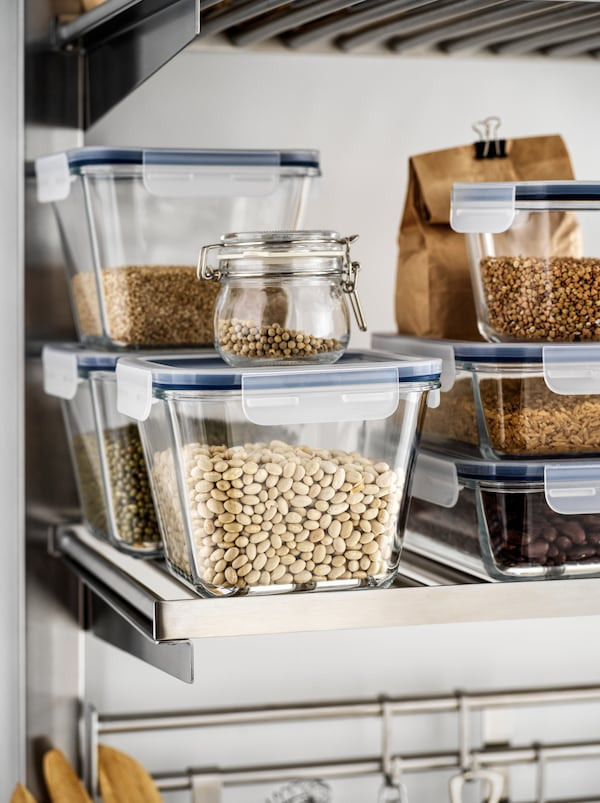 Various dry goods – beans, lentils, grains – in IKEA 365+ glass food containers stacked on a metal kitchen shelf.
