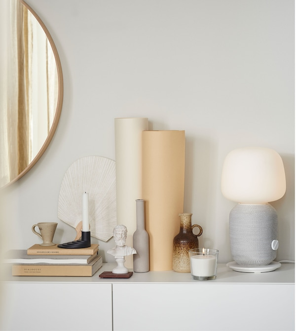 Various earthy coloured ornaments placed on a white surface, including a grey and white SYMFONISK table lamp.